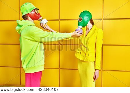 Love and the apocalypse. Two tender lovers in bright clothes and gas masks touch hands for gas masks each other by a yellow industrial wall. Environmental disaster.