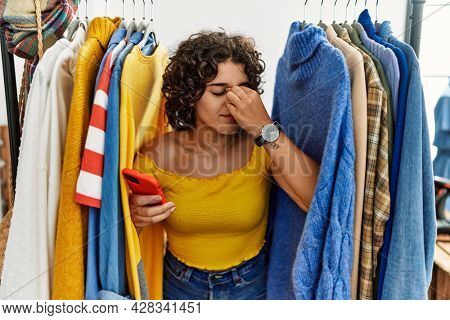 Young hispanic woman searching clothes on clothing rack using smartphone tired rubbing nose and eyes feeling fatigue and headache. stress and frustration concept.