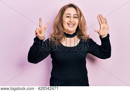 Middle age caucasian woman wearing casual clothes showing and pointing up with fingers number seven while smiling confident and happy.