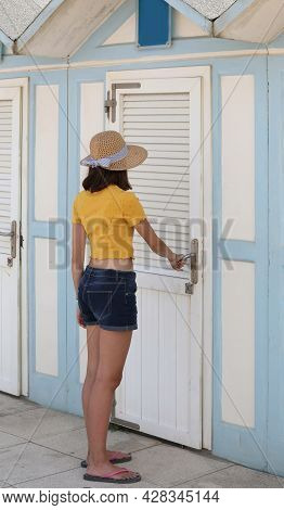 Young Skinny Girl With Straw Hat And Yellow T-shirt Walks Into The Beach Dressing Room To Wear A Swi