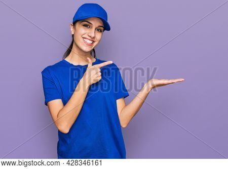 Young hispanic girl wearing delivery courier uniform amazed and smiling to the camera while presenting with hand and pointing with finger.
