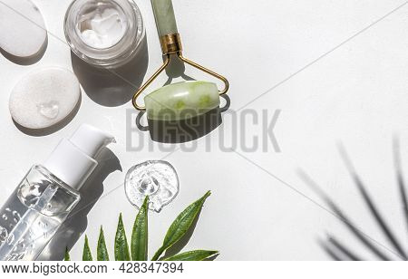 Cream Face Serum On A White Table. Palm Leaf And Shadow Leaves And Face Massage Roller. Face Care Co
