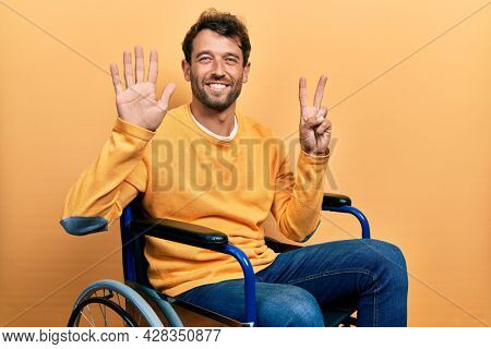Handsome man with beard sitting on wheelchair showing and pointing up with fingers number seven while smiling confident and happy.