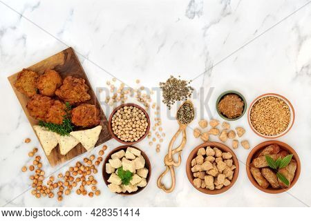 Vegan health food for a healthy diet with tofu bean curd, bhajis,  samosas, tvp, miso, soybeans, chickpeas. Plant based health foods for ethical eating concept. On marble, flat lay top view.