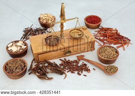 Traditional Chinese herbs and spice used in herbal plant medicine with apothecary old weighing brass scales. Natural health care concept.