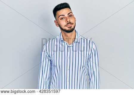 Young hispanic man with beard wearing casual striped shirt smiling looking to the side and staring away thinking.