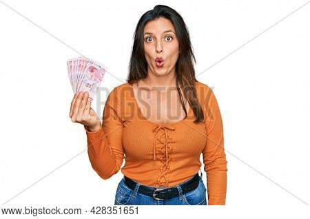 Beautiful hispanic woman holding 50 turkish lira banknotes scared and amazed with open mouth for surprise, disbelief face