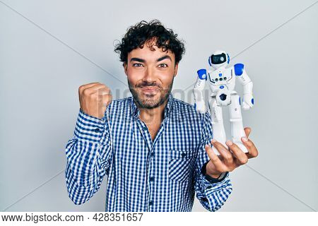 Young hispanic man holding robot toy screaming proud, celebrating victory and success very excited with raised arm