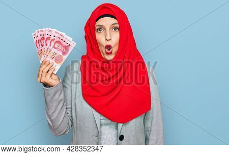 Beautiful hispanic woman wearing islamic hijab holding chinese yuan banknotes scared and amazed with open mouth for surprise, disbelief face