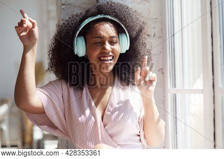 Happy Hilarious Black Multiracial Lady Wearing Headphones Near The Window