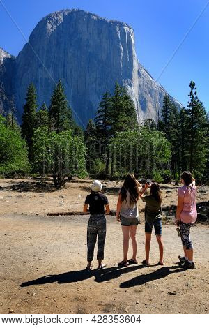 Yosemite National Park view of El Capitan cliff with pine trees and sky and tourists