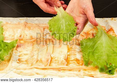 Female Hands Lay Green Fresh Lettuce Leaves On Pita Bread With Sauce On A Black Wooden Table Close-u