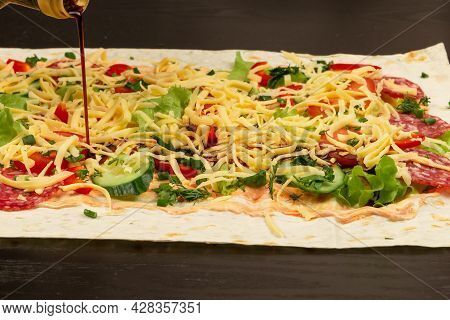 Soy Sauce Is Poured From The Bottle On The Unwrapped Shawarma With Fresh Herbs, Cheese And Vegetable
