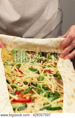 Female Hands Wrap Fresh Vegetable Salad With Cheese In Pita Bread. Cooking Shawarma On A Black Woode