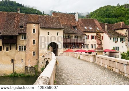 St. Ursanne, Switzerland - July 5th 2021: Bridge Over The Doubs River, Skyline And Entrance Gate To