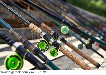 Many Fishing Rods On The Wooden Pier By The River Or Lake On A Sunny Day