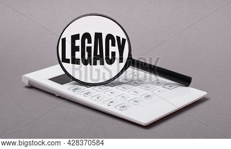 On Gray Background Black Calculator And Magnifier With Text Legacy. Business Concept