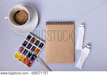 Artists Table With Sketchbook, Watercolors, Brushes, And A Cup Of Coffee. Layout Of The Artist. Beau