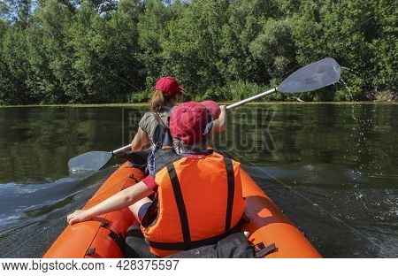 People In An Inflatable Kayak On The Water In Motion