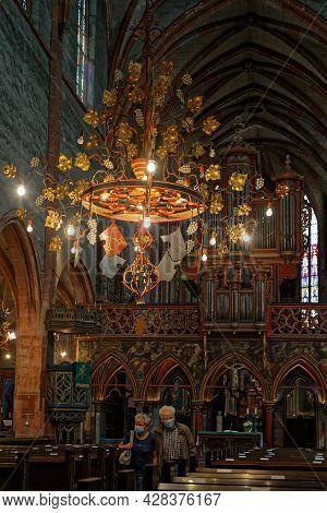 Strasbourg, France, June 24, 2021 : Old Couple Walk In Saint-pierre-le-jeune Protestant Church Main