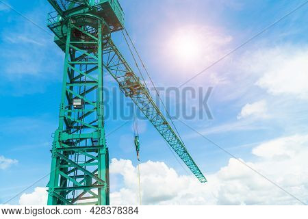Green Hoisting Crane On Blue Sky Background With Clouds, Close Up Of The Tower Crane. The Constructi
