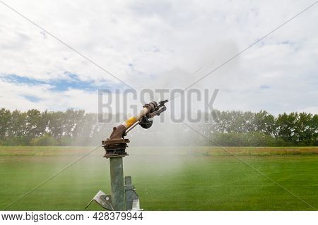 Sprinkler Watering Agricultural Field In The Sun Irrigation Plant In Agriculture Under Bright Sunlig