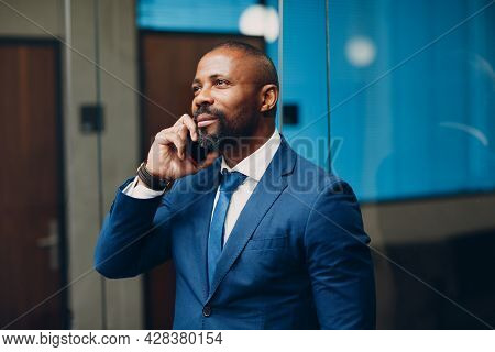 Portrait Smiling African American Businessman In Blue Suit In Office With Mobile Phone Speaking Talk