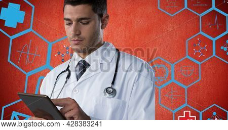 Composition of male doctor using tablet over digital icons on red background. flu, sickness, virus and vaccination concept digitally generated image.