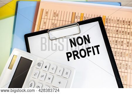 A Non-profit Organization Is Written On A Stationery Tablet That Lies On A Folder With A Financial D