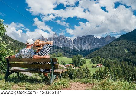 Hugging Couple Dressed Striped White Tops Sitting On Bench Enjoying Santa Maddalena Village View And