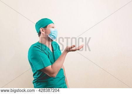 Young Doctor Portrait In Green Surgeon Suit And Protective Breathing Mask With Nothing In His Hand O