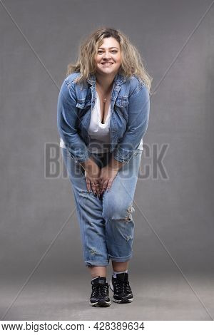 Beautiful Plump Woman In A Denim Suit On A Gray Background.