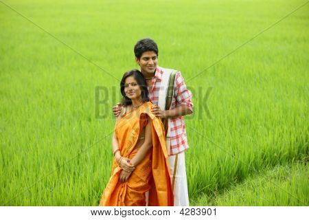 Couple Standing In A Paddy Field