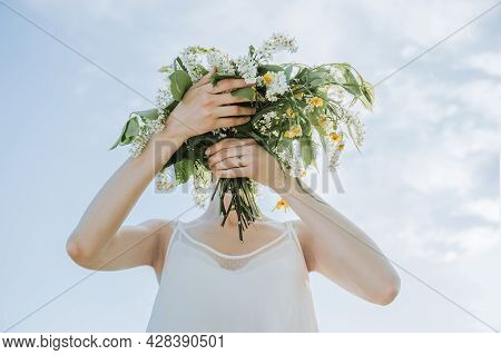 Girl With A Head Bouquet Of Wildflowers. Surreal Portrait. Pretty Female Hands Holding Bouquet Of Wi