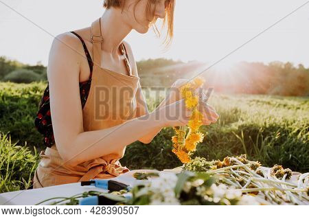 Florist Workshop. Pretty Woman Making Wreath From Dandelions. Romantic Background Of Florist At Work