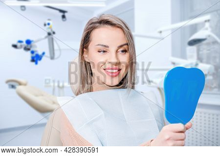 Happy Attractive Woman Looking At Her Teeth In Mirror. Satisfied Patient Of Dental Care Or Whitening