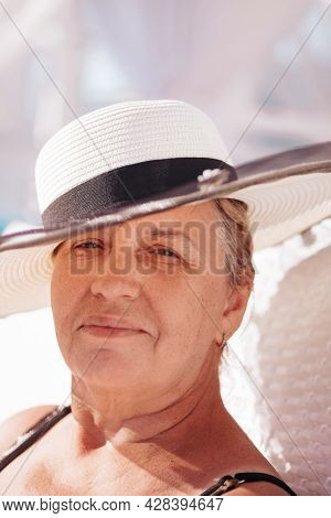 A Woman In A Straw Hat. Close-up Portrait Of An Elderly, Happy Woman In A White Straw Hat Resting In
