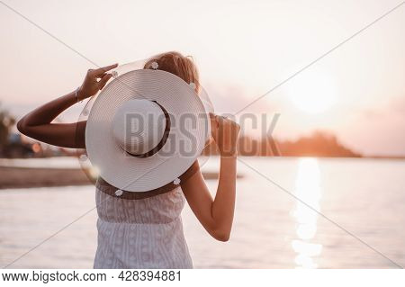 A Woman With A Hat At Sunset Rear View. A Young Blonde In A Summer Sundress And A Straw Hat Decorate