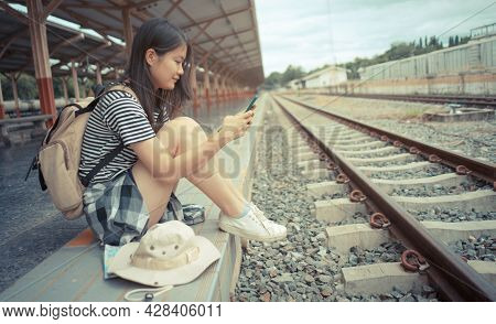 Concept Of Travel And Tourism. Young Asian Female Tourist Uses A Mobile Phone While Waiting For A Tr