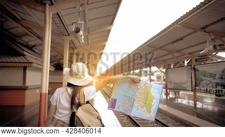 Young Girl Tourist Carrying A Bag And Holding Map Hitchhiking The Train On The Railway At The Train