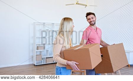 Couple of guy and blonde lady holds cardboard boxes and puts on large pile in new apartment after moving with happy smiles