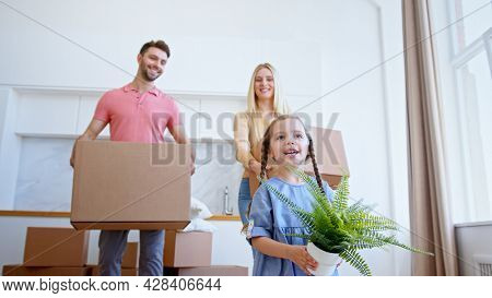 Funny little preschooler daughter looks at parents walking along new apartment with green pot plant and happy smile low angle shot