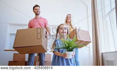 Delighted family parents and preschooler daughter move to new apartment holding brown cardboard boxes and pot plant low angle shot