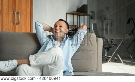 Smiling cyborg guy with bio limb prothesis with cheerful laughter at home