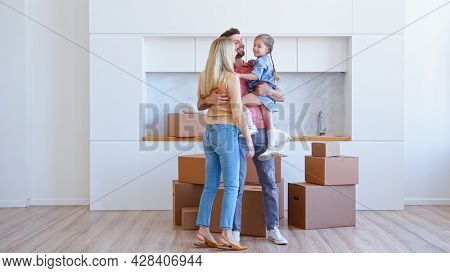 Joyful family with kid girl carries different cardboard boxes into new apartment and puts on large pile on brown wooden floor dancing