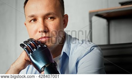 Serious cyborg disabled man with bio prothesis thinks holding head on hands sitting against blurred bookshelf at home extreme closeup