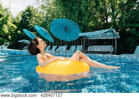 Sexy Brunette Millennial On An Inflatable Ring Swims In The Swimming Pool In A Modern Hotel. Girl Ta