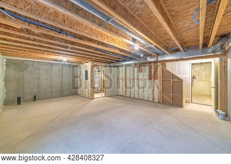 Empty Unfinished Large Basement With Concrete Flooring And Wooden Frames