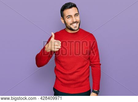 Young hispanic man wearing casual clothes doing happy thumbs up gesture with hand. approving expression looking at the camera showing success.