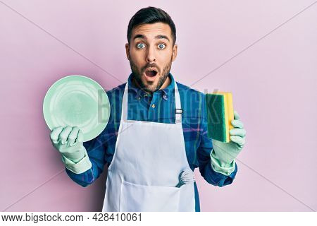 Young hispanic man wearing apron holding scourer washing dishes afraid and shocked with surprise and amazed expression, fear and excited face.